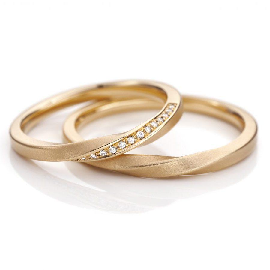 Die Drehung - schmale Ringe aus 750 Roségold, der Damenring ist mit Diamanten besetzt